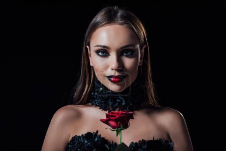 Photo pour Souriant effrayant vampire fille en robe gothique noire tenant rose rouge isolé sur noir - image libre de droit