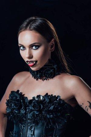 Photo pour Effrayant vampire fille avec crocs dans noir gothique robe regarder caméra isolé sur noir - image libre de droit