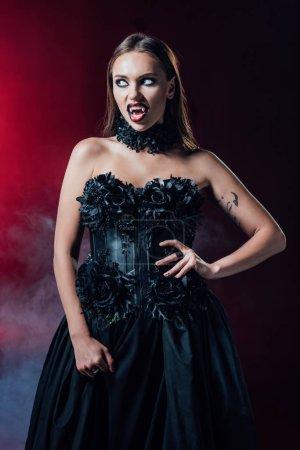 Photo pour Effrayant vampire fille avec crocs en robe gothique noire sur fond noir avec de la fumée - image libre de droit