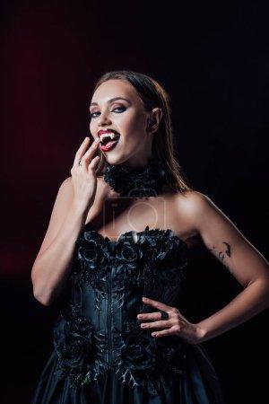 Photo pour Fille vampire effrayante avec des accroches en robe gothique noire isolée sur noir - image libre de droit