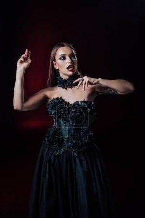 Photo pour Effrayant vampire fille avec crocs en robe gothique noire sur fond noir - image libre de droit
