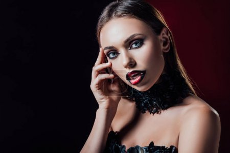 Photo pour Scary vampire girl with fangs in black gothic dress on black background - image libre de droit