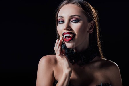 Photo pour Naked scary vampire girl showing fangs isolated on black - image libre de droit