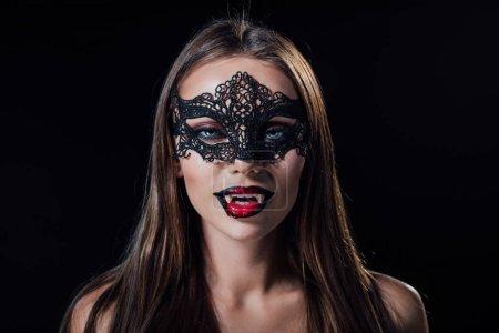 Photo pour Nu effrayant vampire fille dans mascarade masque montrant crocs isolé sur noir - image libre de droit