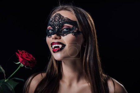 Photo pour Nu effrayant vampire fille dans mascarade masque montrant crocs et tenant rose isolé sur noir - image libre de droit