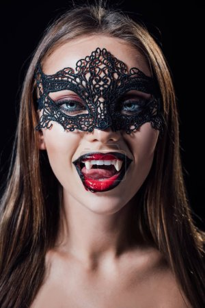Photo pour Naked scary vampire girl in masquerade mask showing fangs isolated on black - image libre de droit