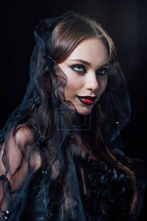 uśmiechnięty straszny wampir dziewczyna w czarny gotycki strój i welon odizolowany na czarny
