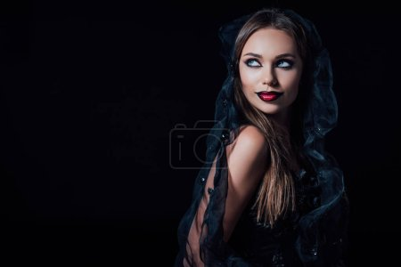 Photo pour Scary vampire girl in black gothic dress and veil looking away isolated on black - image libre de droit