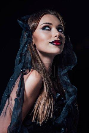 Photo pour Smiling vampire fille en robe gothique noire et voile isolée sur noir - image libre de droit