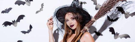 Photo pour Photo panoramique d'une jeune fille en sorcière noire costume d'Halloween avec balai près d'un mur blanc avec chauves-souris décoratives - image libre de droit