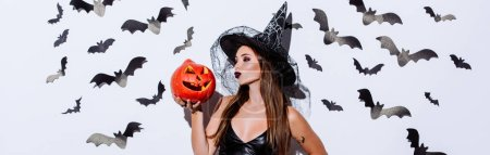 Photo pour Photo panoramique d'une jeune fille en sorcière noire costume d'Halloween baisant citrouille sculptée près d'un mur blanc avec des chauves-souris décoratives - image libre de droit