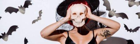 Photo pour Photo panoramique d'une jeune fille en sorcière noire costume d'Halloween avec des cheveux rouges tenant le crâne devant le visage près d'un mur blanc avec des chauves-souris décoratives - image libre de droit