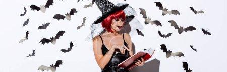 Photo pour Photo panoramique d'une jeune fille en costume de sorcière noire de l'Halloween avec des cheveux rouges livre de lecture près d'un mur blanc avec des chauves-souris décoratives - image libre de droit