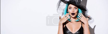 Photo pour Panoramic shot of shocked girl in black witch Halloween costume with blue hair on white background - image libre de droit