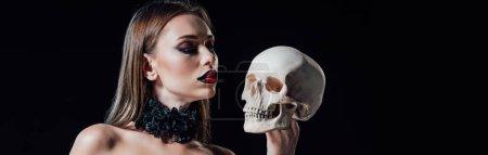 Photo pour Plan panoramique de fille vampire effrayant en robe gothique noire regardant le crâne humain isolé sur noir - image libre de droit
