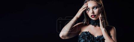 Photo pour Plan panoramique de vampire effrayant fille en robe gothique noire touchant visage isolé sur noir - image libre de droit