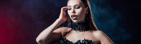 Photo pour Plan panoramique de vampire effrayant fille avec crocs en robe gothique noire sur fond noir avec de la fumée - image libre de droit