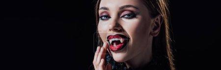 Photo pour Plan panoramique de vampire effrayant fille montrant crocs en robe gothique noire isolé sur noir - image libre de droit