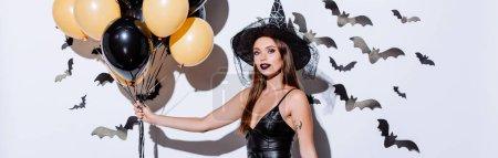 Photo pour Plan panoramique de fille en costume d'Halloween sorcière noire tenant des ballons près du mur blanc avec des chauves-souris décoratives - image libre de droit