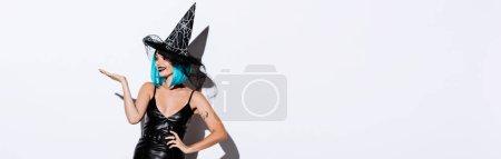 Photo pour Plan panoramique de fille heureuse en costume noir d'Halloween sorcière avec les cheveux bleus pointant avec la main sur fond blanc - image libre de droit