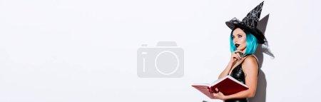Photo pour Plan panoramique de fille sexy coûteuse en costume d'Halloween sorcière noire avec livre de détention de cheveux bleus sur fond blanc - image libre de droit