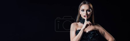 Photo pour Panoramic shot of scary vampire girl in black gothic dress showing shh sign isolated on black - image libre de droit