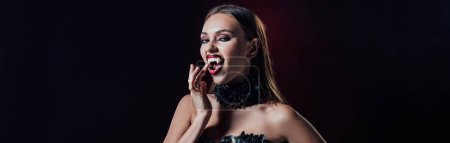 Photo pour Panoramic shot of scary vampire girl showing fangs in black gothic dress isolated on black - image libre de droit