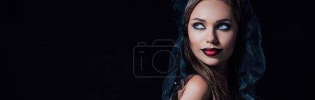 Photo pour Plan panoramique de fille vampire effrayant en robe gothique noire et voile regardant loin isolé sur noir - image libre de droit