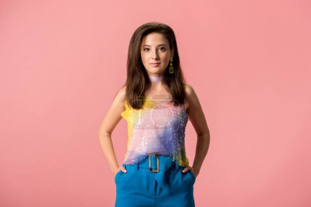 Photo pour Jeune fille disco élégante avec les mains dans des poches isolées sur rose - image libre de droit