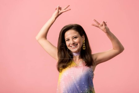 Photo pour Happy young stylish disco girl showing peace sign isolated on pink - image libre de droit