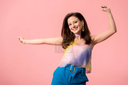 Photo pour Happy young stylish disco girl dancing isolated on pink - image libre de droit