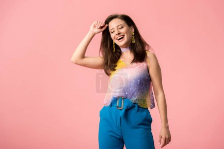 Photo pour Excited young stylish disco girl dancing isolated on pink - image libre de droit