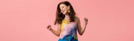 Photo pour Panoramic shot of excited young stylish disco girl dancing isolated on pink - image libre de droit