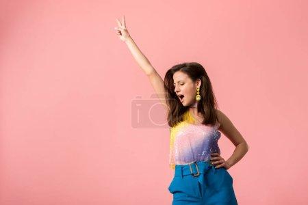 Photo pour Jeunes filles excitées de disco élégant dansant main dans l'air isolé sur rose - image libre de droit
