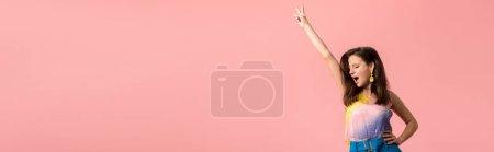 Photo pour Photo panoramique de jeunes discothèques excitantes dansant à la main dans l'air isolé sur rose - image libre de droit