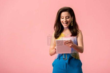 Photo pour Excité jeune fille disco élégant tenant tablette numérique isolé sur rose - image libre de droit