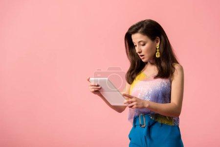 sorprendido joven elegante disco chica sosteniendo tableta digital aislado en rosa