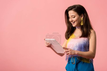 Photo pour Smiling young stylish disco girl holding digital tablet isolated on pink - image libre de droit