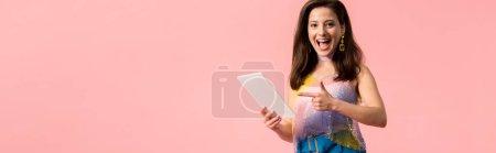 Panoramaaufnahme eines aufgeregten jungen stilvollen Disco-Mädchens, das mit dem Finger auf ein digitales Tablet zeigt, isoliert auf rosa