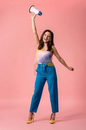 Photo pour Joyeuse jeune discothèque avec mégaphone sur rose - image libre de droit