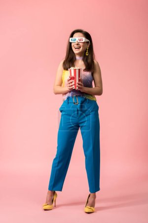 Photo pour Full length view of happy young stylish disco girl in 3d glasses holding striped paper bucket with popcorn on pink - image libre de droit