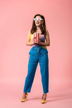 Photo pour Vue pleine longueur d'une jeune discothèque joyeuse et élégante en verres 3d tenant un seau en papier rayé avec du maïs soufflé sur du rose - image libre de droit