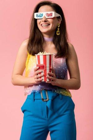 Photo pour Joyeuse jeune discothèque de style dans des verres 3d tenant un seau rayé en papier avec du maïs soufflé isolé sur rose - image libre de droit