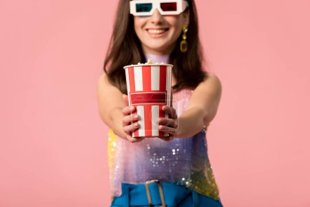 Photo pour Selective focus of happy young stylish disco girl in 3d glasses presenting striped paper bucket with popcorn isolated on pink - image libre de droit