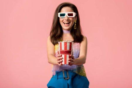 Photo pour Heureux jeune fille disco élégant dans des lunettes 3D tenant seau en papier rayé avec pop-corn isolé sur rose - image libre de droit