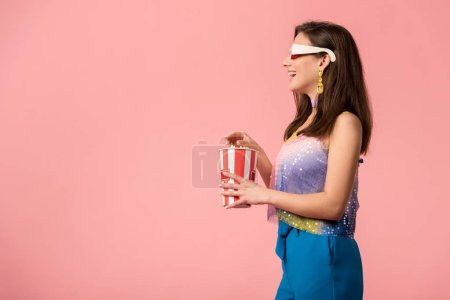Photo pour Side view of happy young stylish disco girl in 3d glasses eating popcorn isolated on pink - image libre de droit