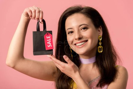 Photo pour Happy stylish disco girl holding shopping bags isolated on pink - image libre de droit