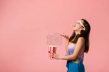 Photo pour Side view of happy young stylish disco girl in 3d glasses throwing popcorn in mouth isolated on pink - image libre de droit