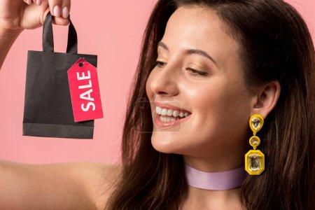 """Photo pour Jolie discothèque tenant un sac avec le lettrage de la vente sur l """"étiquette isolée en rose - image libre de droit"""