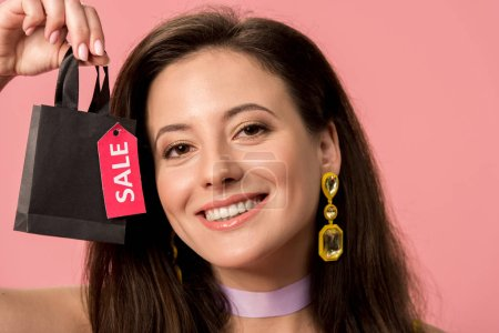 Photo pour Happy stylish disco girl holding shopping bag with sale lettering on label isolated on pink - image libre de droit
